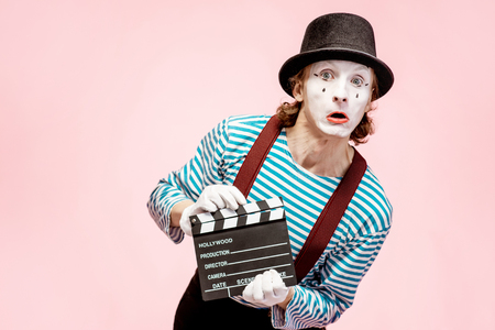 Photo pour Portrait of an actor as a pantomime with cinematography clapperboard on the pink background - image libre de droit
