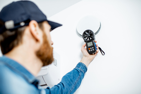 Photo pour Handyman checking the speed of air ventilation with measuring tool on the white wall background - image libre de droit