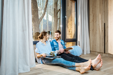 Photo pour Happy couple sitting together on the floor near the window with beautiful view, reading some magazines and relaxing at home - image libre de droit