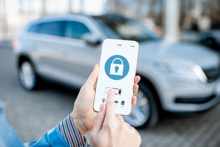 Photo pour Locking car using mobile application on a smart phone. Concept of remote control and car protection through the internet - image libre de droit