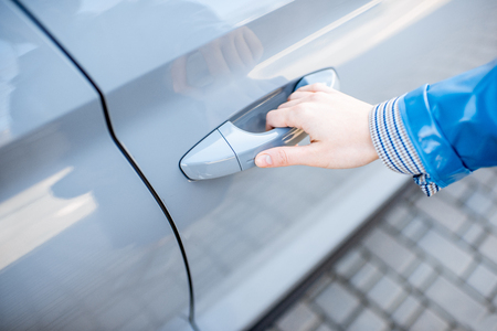 Foto de Woman pulling door handle of the modern car, close-up view. Concept of the keyless access to the car - Imagen libre de derechos