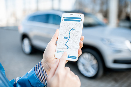 Foto de Woman using smart phone with navigation app, close-up view with modern car on the background - Imagen libre de derechos