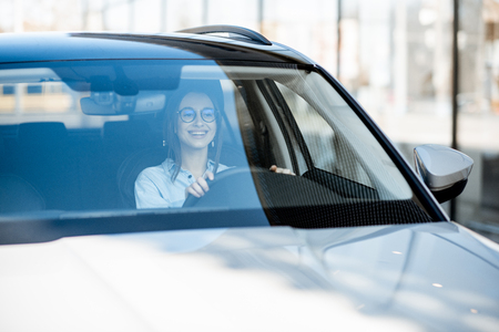 Photo pour Young and happy woman driving a luxury car in the city, front view through the windshield - image libre de droit