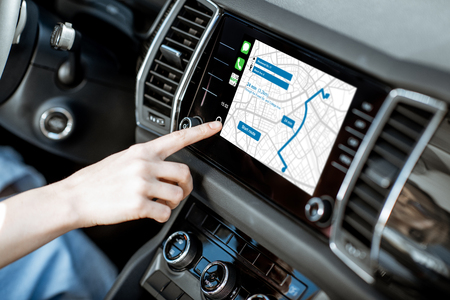 Foto de Touching a monitor with navigation map of the modern car, close-up view - Imagen libre de derechos