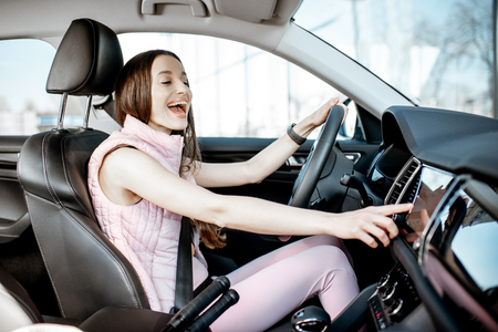 Foto de Young and cheerful woman in pink sportswear listening to the music while driving luxury car in the city - Imagen libre de derechos