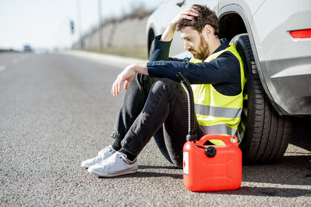 Photo pour Man with despair emotions sitting with refuel canister near his car on the roadside - image libre de droit