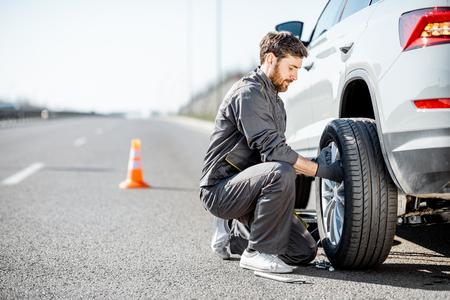 Foto de Handsome road assistance worker in uniform changing car wheel on the highway - Imagen libre de derechos