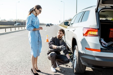 Photo pour Road assistance worker helping young woman to change a car wheel on the highway - image libre de droit