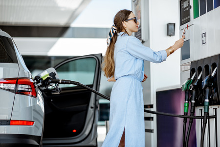 Photo pour Woman paying with phone for gasoline, photographing bar code on the gas station pump - image libre de droit