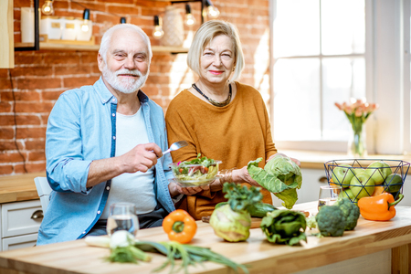 Photo pour Cheerful senior couple eating salad standing together with healthy food on the kitchen at home. Concept of healthy nutrition in older age - image libre de droit