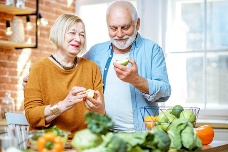 Foto de Portrait of a cheerful senior couple eating apples standing together with healthy food on the kitchen at home - Imagen libre de derechos