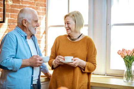 Photo pour Portrait of a lovely senior couple talking together, standing with coffee cups near the window at home - image libre de droit