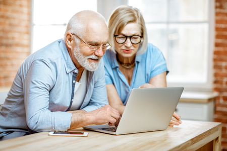 Photo pour Portrait of a beautiful senior couple in blue shirts feeling happy, sitting together with laptop at home - image libre de droit