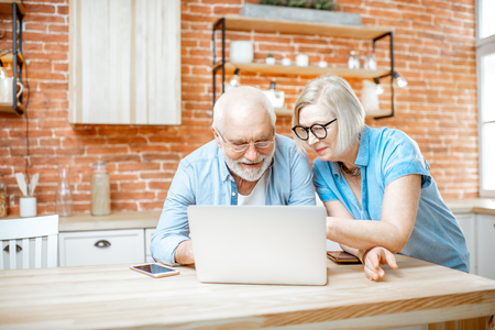 Foto de Beautiful senior couple in blue shirts sitting together with laptop on the kitchen at home - Imagen libre de derechos