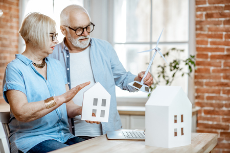 Photo pour Senior couple dreaming about modern property and alternative energy, sitting with house models and toy wind turbine at home - image libre de droit
