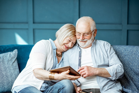 Foto de Lovely senior couple dressed casually using digital tablet while sitting together on the comfortable couch at home - Imagen libre de derechos