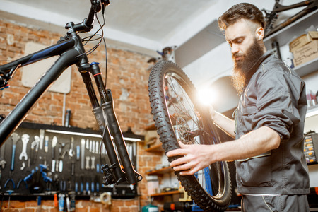 Photo pour Handsome repairman in workwear serving mountain bicycle, standing with front wheel at the workshop of a bicycle shop - image libre de droit