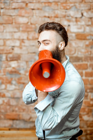 Photo pour Handsome bearded man with red loudspeaker on the brick wall background - image libre de droit