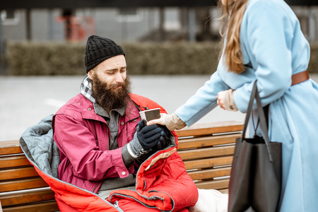 Photo pour Woman helping homeless beggar giving some hot drink outdoors. Concept of helping poor people - image libre de droit