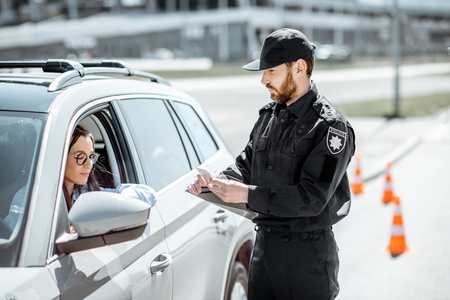 Foto de Policeman checking documents of a young female driver standing near the car on the roadside in the city - Imagen libre de derechos