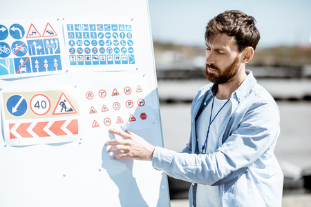 Photo pour Male instructor showing traffic signs on a flip chart standing on the training ground at the drivers school - image libre de droit