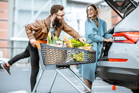 Foto de Young stylish couple with shopping cart full of fresh food, packing products into the car on the outdoor parking - Imagen libre de derechos