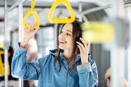 Photo pour Young stylish woman enjoying trip in the public transport, standing with headphone while moving in the modern tram - image libre de droit