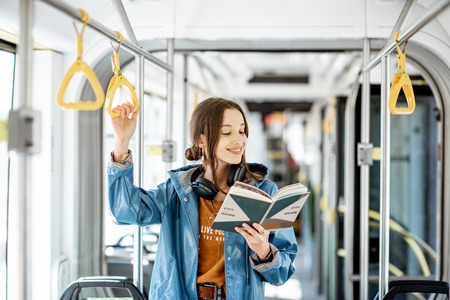 Photo pour Young woman reading book while standing in the modern tram, happy passenger moving by comfortable public transport - image libre de droit