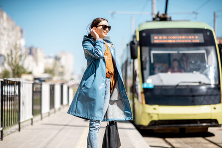 Foto de Young woman in blue coat waiting for the tram on the station outdoors - Imagen libre de derechos