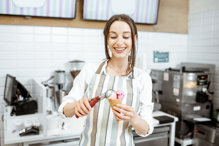 Photo for Young and happy saleswoman in apron making ice cream at the counter of the modern pastry shop indoors - Royalty Free Image