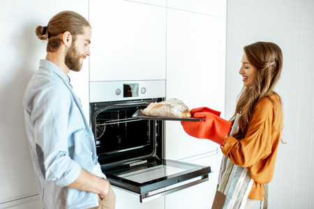 Foto de Young and cheerful couple baking breads at the modern white kitchen at home - Imagen libre de derechos