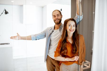 Foto de Portrait of a young couple standing together at the new modern studio. Concept of happy real estate owners - Imagen libre de derechos