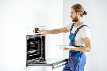 Photo pour Handsome workman in overalls setting up electric oven on the kitchen at home - image libre de droit