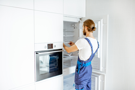Photo pour Handsome workman installing new refrigerator in the modern kitchen at home - image libre de droit
