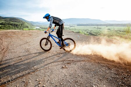 Photo for Professional well-equipped cyclist riding extremely on the rocky mountains raising dust behind during the sunset - Royalty Free Image