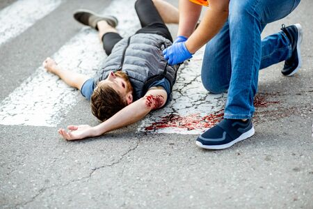Foto de Man applying first aid to the injured bleeding person, wearing tourniquet on the arm after the road accident on the pedestrian crossing - Imagen libre de derechos