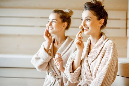 Photo for Young women taking care of their skin, making facial massage in the SPA, sitting together in bathrobes - Royalty Free Image