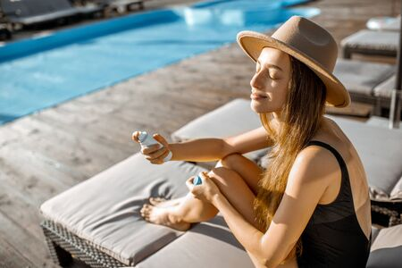 Foto de Young woman spraying water on her face while relaxing on the sunbed near the swimming pool - Imagen libre de derechos