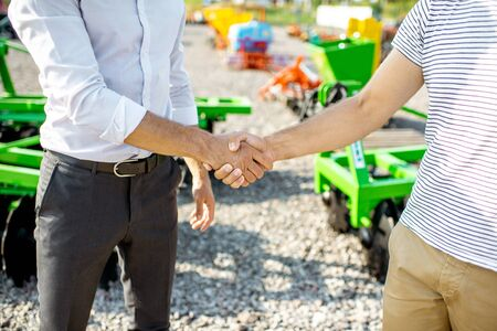 Photo pour Buyer shaking hand with salesman on the open ground of the agricultural shop, having a deal, close-up view - image libre de droit