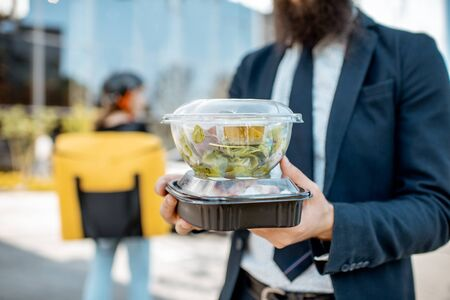 Photo for Businessman holding lunch boxes with takeaway food received from a courier outdoors. Food delivery concept - Royalty Free Image