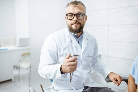 Photo for Portrait of a senior otolaryngologist in medical gown with ENT flushing tool in the procedure room - Royalty Free Image