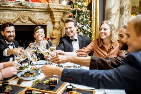 Foto de Elegantly dressed group of people having fun, clinking wine glasses during a festive dinner near the fireplace and christmas tree, celebrating New Year holiday at the luxury restaurant - Imagen libre de derechos