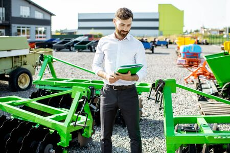 Photo pour Portrait of a handsome salesman standing near the plow at the outdoor ground of the shop with new agricultural machinery - image libre de droit