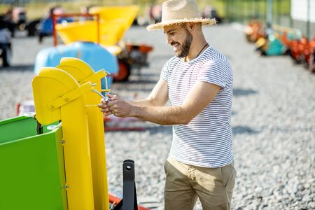Photo pour Agronomist choosing a new planter for farming at the outdoor ground of the shop with agricultural machinery - image libre de droit