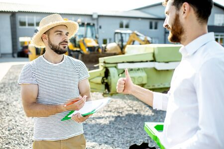 Photo pour Young agronomist with salesman or manager at the open ground of the shop with agricultural machinery - image libre de droit