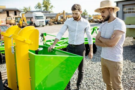 Photo pour Young agronomist with salesman at the open ground of the shop with agricultural machinery, buying a new planter for farming - image libre de droit