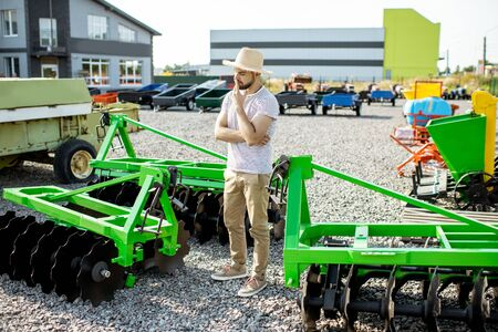 Photo pour Portrait of a thoughtful agronomist standing near the plow at the outdoor ground of the shop, choosing new agricultural machinery for farming - image libre de droit