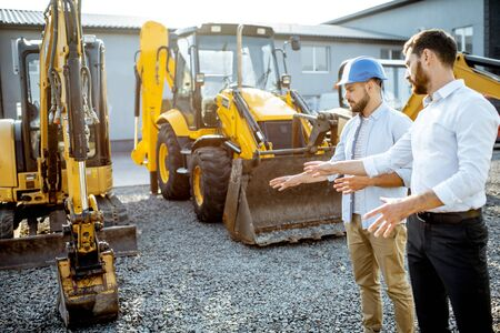 Foto de Builder choosing heavy machinery for construction with a sales consultant on the open ground of a shop with special vehicles - Imagen libre de derechos