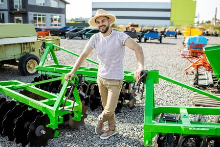 Photo pour Portrait of a young agronomist standing near the plow at the outdoor ground of the shop, buying new agricultural machinery for farming - image libre de droit