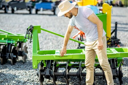Photo pour Agronomist choosing a new plow for farming at the outdoor ground of the shop with new agricultural machinery - image libre de droit